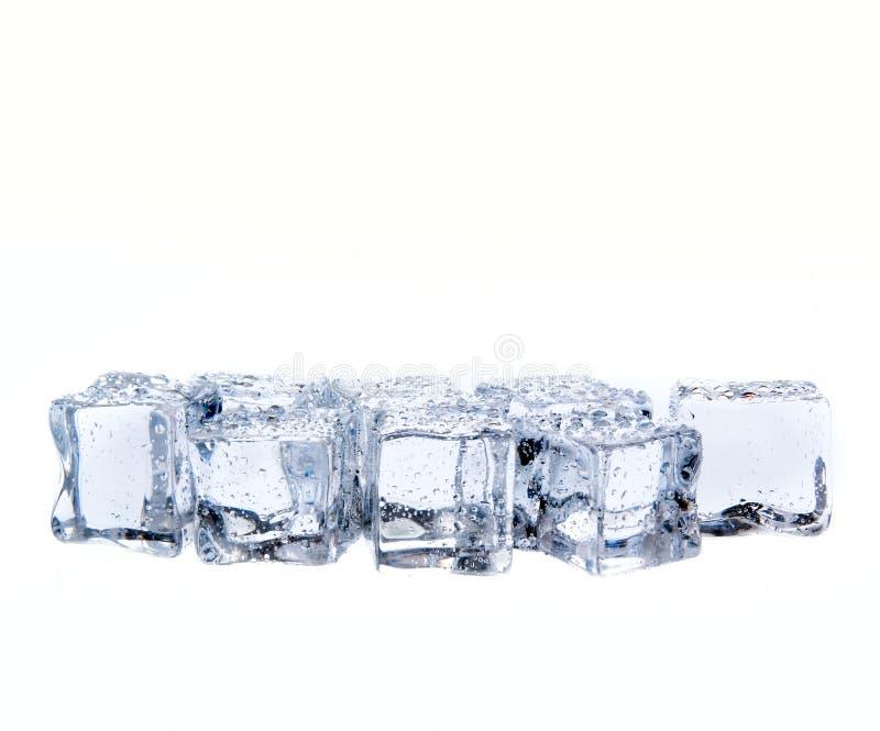 Kostki lodu z wodnymi kroplami odizolowywać na bielu fotografia royalty free