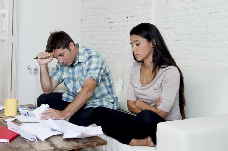 Kostnader för månadstidning för ung ledsen hemmastadd vardagsrumsoffa för par oroade beräknande i spänning arkivbilder