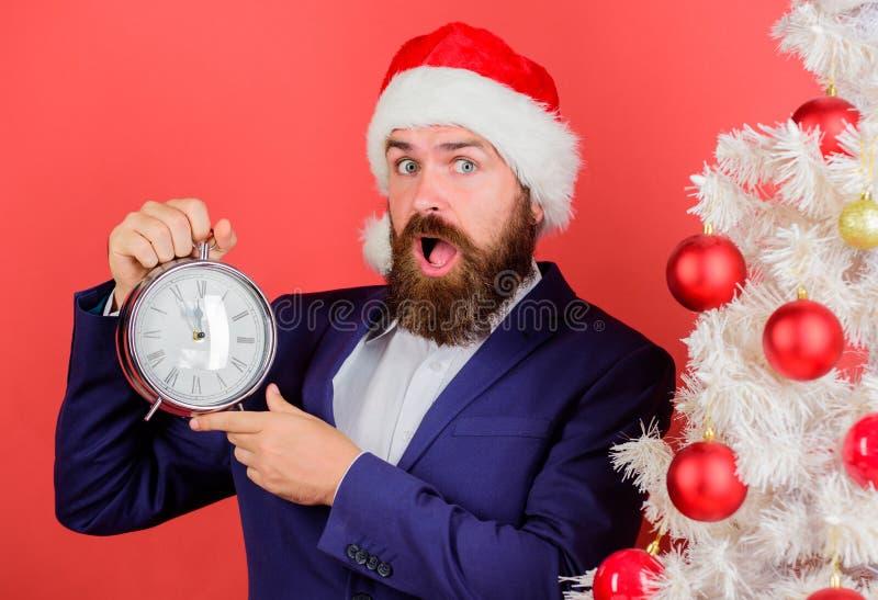 Kostuum van de mensen het gebaarde slijtage en de greepklok van de santahoed De zakenman sluit zich aan Kerstmis bij viering De o stock afbeeldingen