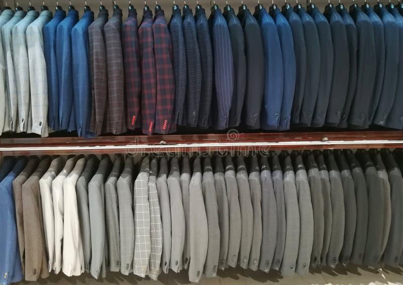 Kostuums voor mensen in een winkel stock afbeelding