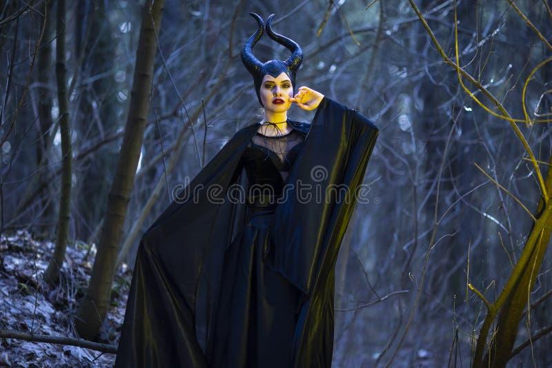 Kostympj?slek Mystisk och magisk Maleficent kvinna med horn som poserar i tom skog f?r v?r med den krabba sjalen arkivfoton
