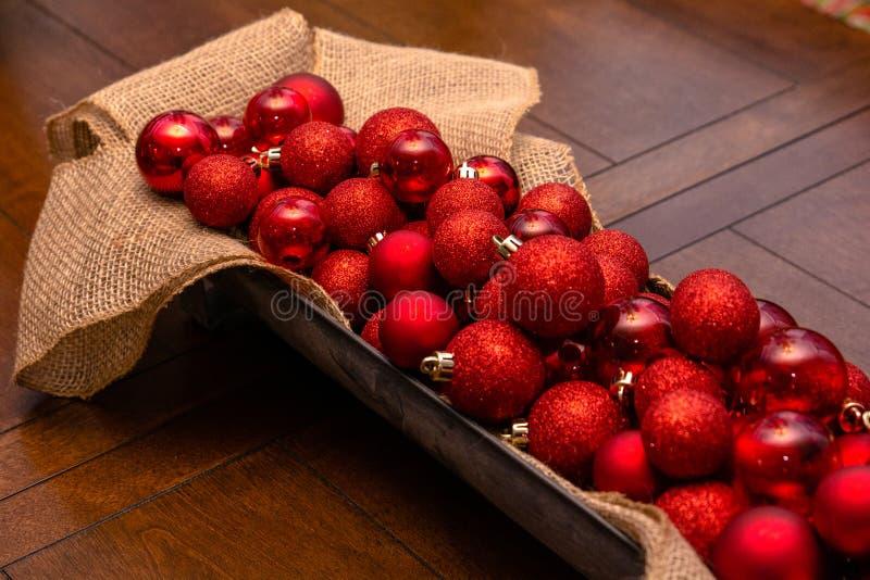 Kosz Czerwoni boże narodzenie ornamenty na stole zdjęcie royalty free