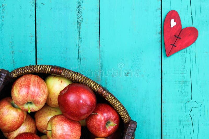 Kosz czerwoni jabłka na drewno stole z czerwonym sercem zdjęcie stock