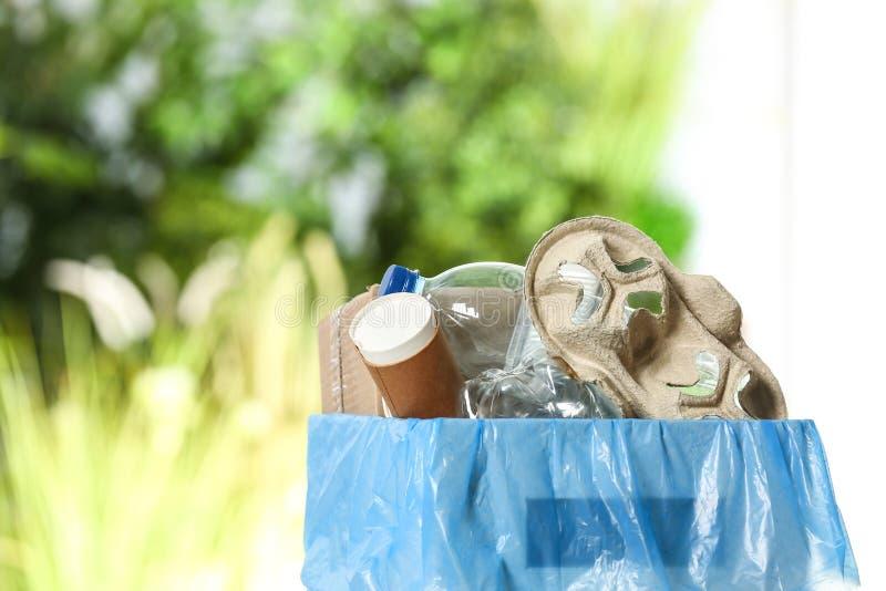 Kosz na śmieci z śmieci na zamazanym tle obraz royalty free