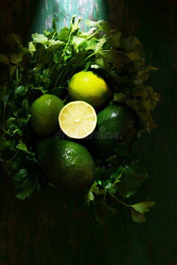 Kosz z świeżymi organicznie zieleniami, avocado i wapnem na ciemnozielonym tle, monochrom obraz stock
