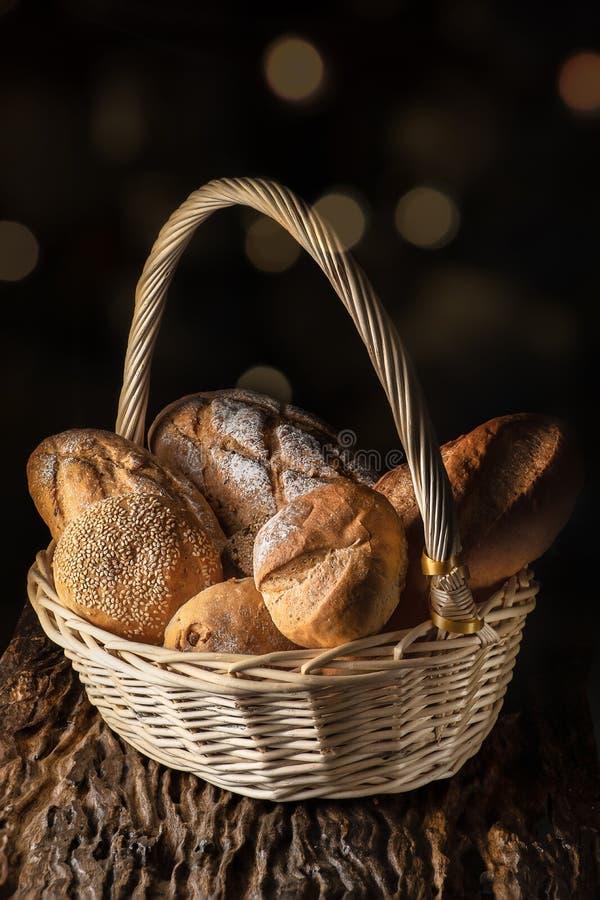 Kosz z asortymentem chleb na drewnianej desce z ciemnym t?em zdjęcie royalty free