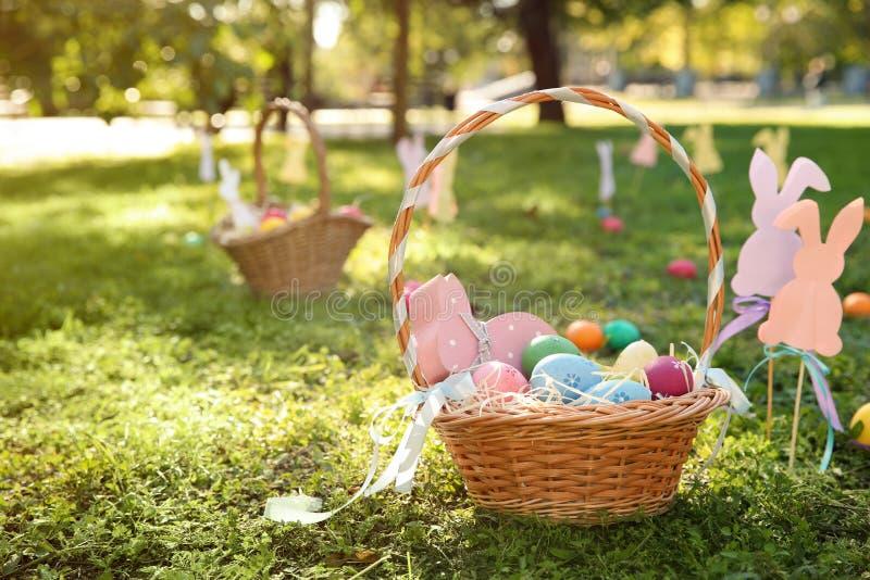 Kosz z Wielkanocnymi jajkami i wystrojem na trawie w parku zdjęcie royalty free