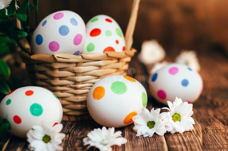Kosz z Wielkanocnymi jajkami malującymi w okręgu, wiosny gałąź z zielonymi liśćmi, obrazy stock
