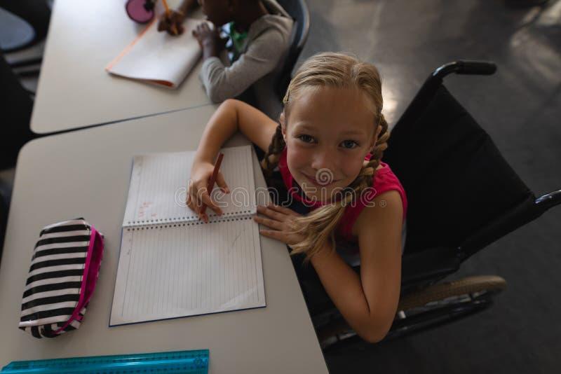 Koszt stały obezwładnia uczennicy patrzeje kamerę podczas gdy siedzący przy biurkiem w sali lekcyjnej fotografia royalty free