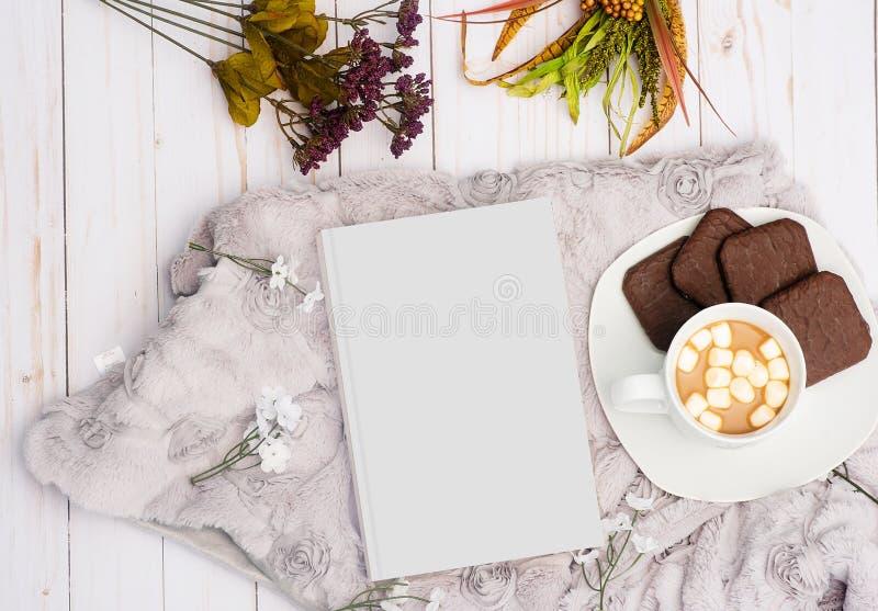 Koszt stały strzał biała książka obok słodkiego napoju z czekoladowymi ciastkami na talerzu obraz royalty free