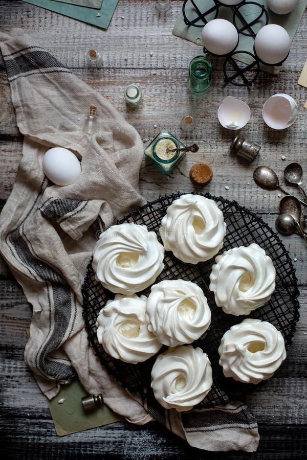 Koszt stały strzał domowej roboty biały mini beza deserów pavlova na łozinowym metalu stojaku na popielatym drewnianym stole z bu zdjęcia stock