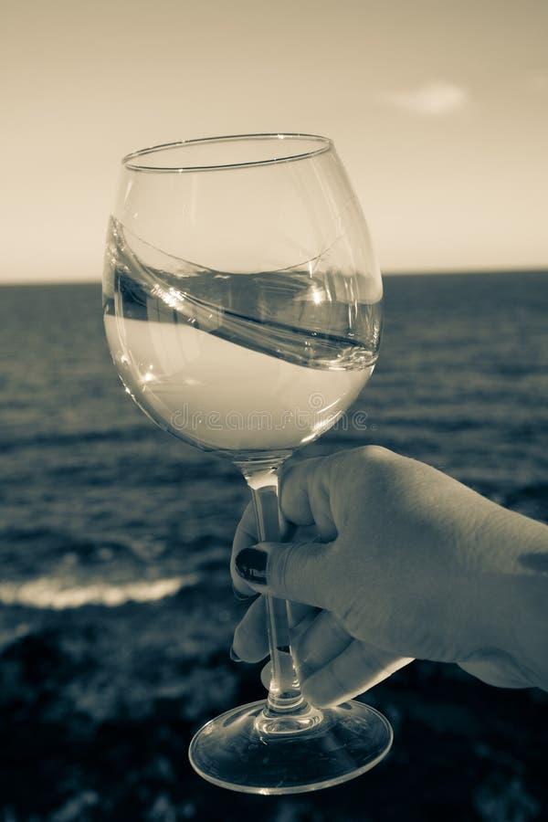 Kosztować szkło zimny biały wino na plenerowym tarasie z morzem fotografia stock