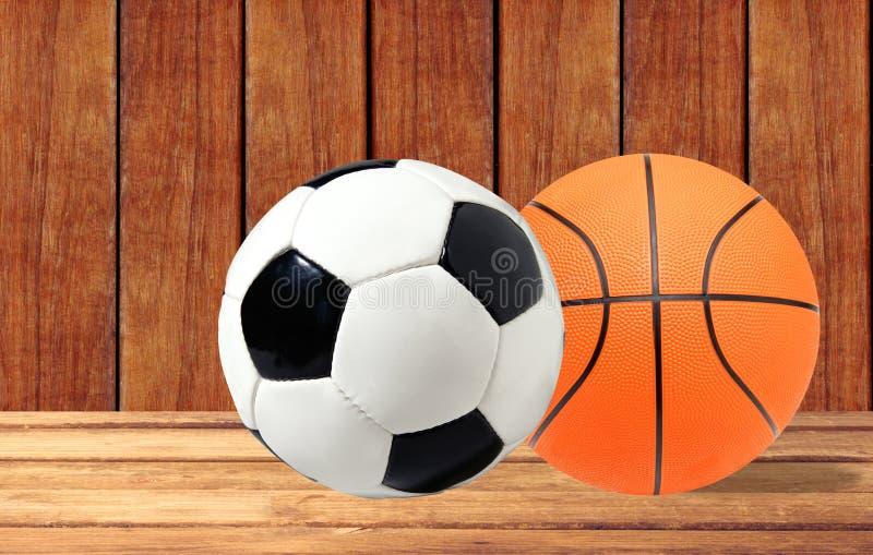 Koszykówki i piłki nożnej piłka na drewnianym stole nad drewnianym backg fotografia royalty free