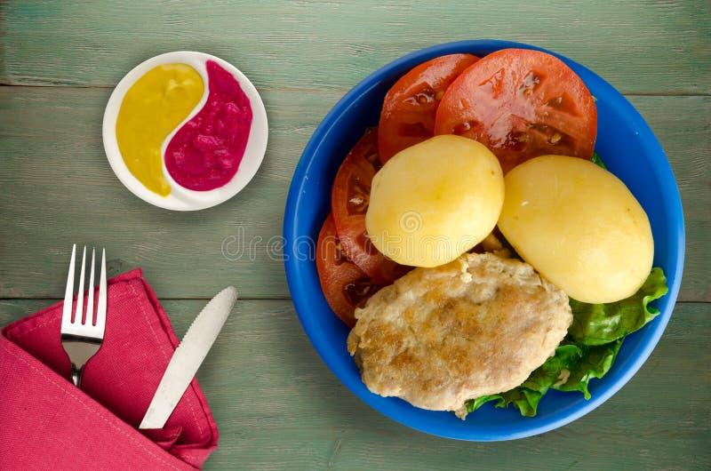 Kotelet met aardappels op een plaat stock afbeelding