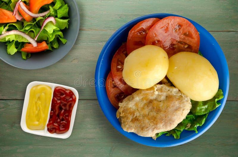 Kotelet met aardappels op een plaat stock fotografie