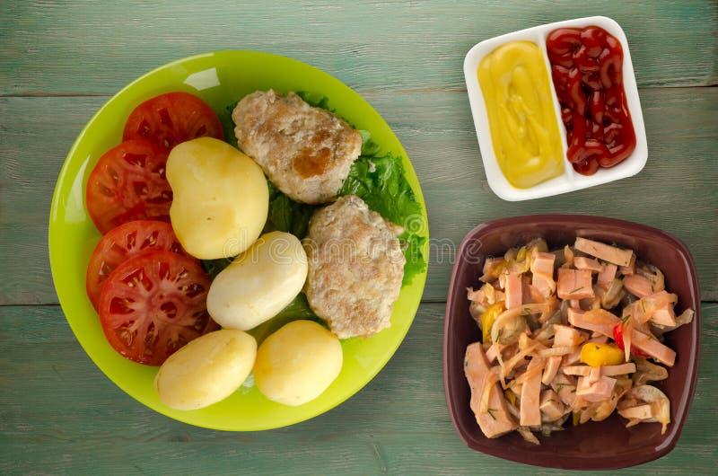 Kotelet met aardappels op een plaat stock afbeeldingen