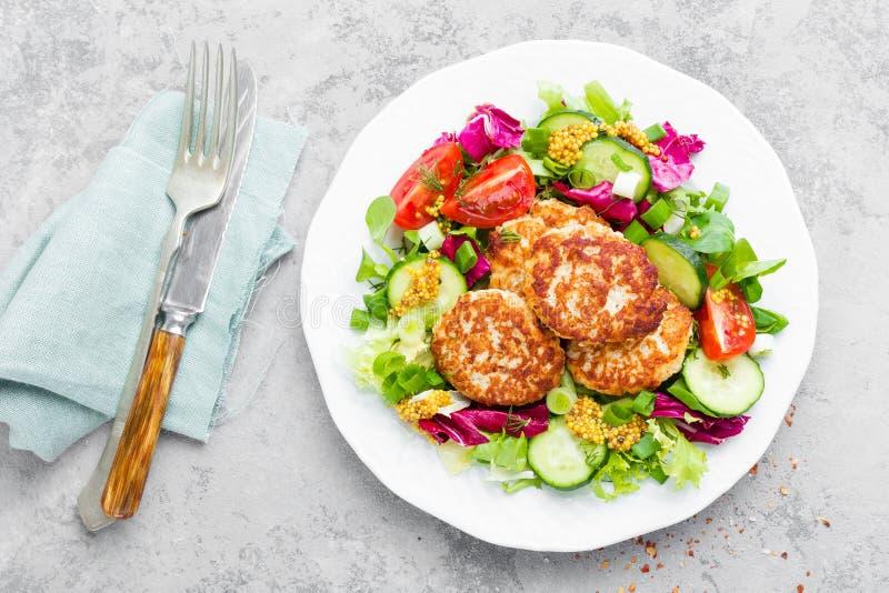 Koteletts und Frischgemüsesalat auf weißer Platte Gebratene Fleischklöschen mit Gemüsesalat lizenzfreie stockfotos