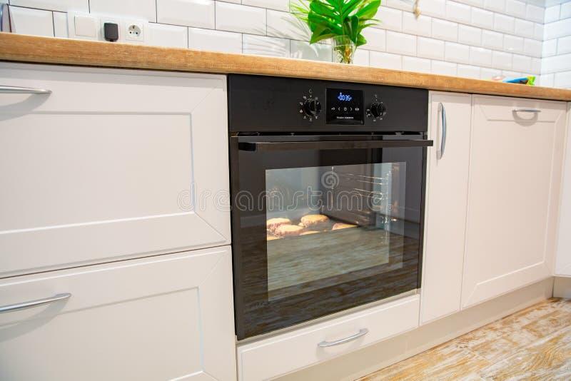 Koteletts werden im Ofen auf weißer moderner Küche gebacken stockfoto