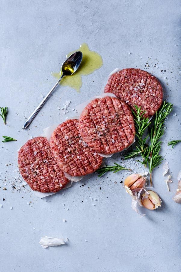 Kotletter för biff för hamburgare för jordnötköttkött rå på grå tabellöverkant arkivbilder