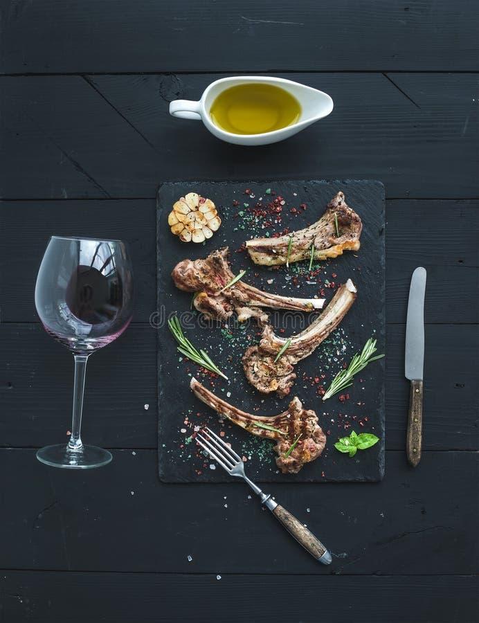 kotletter grillad lamb Kuggen av lammet med vitlök, rosmarin, kryddor kritiserar på magasinet, vinexponeringsglas, olja i ett tef royaltyfri bild