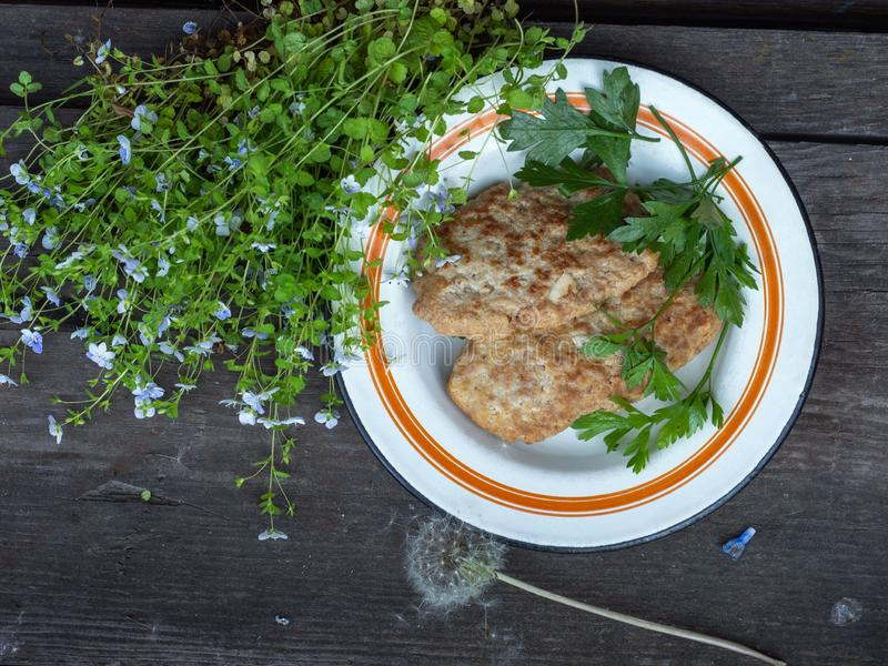Kotletter på en platta för runt järn med hemlagade kotletter på en lantlig tabell för strom En liten bukett av små vildblommor dä fotografering för bildbyråer
