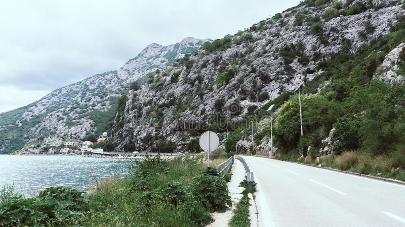 Kotor bay road with big grey rocks and green brush and blue sea. Amazing view of asphalt countryside road and mountain stock photography