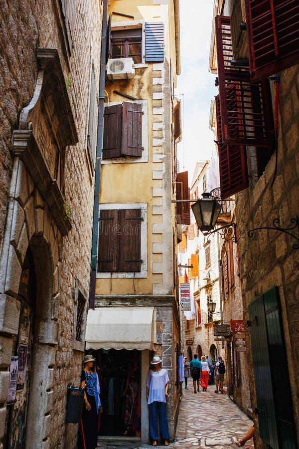 Kotor Montenegro - Augusti 10, 2015: Sikten av en smal gata med talrikt shoppar i gammal stad av Kotor, Montenegro royaltyfri bild