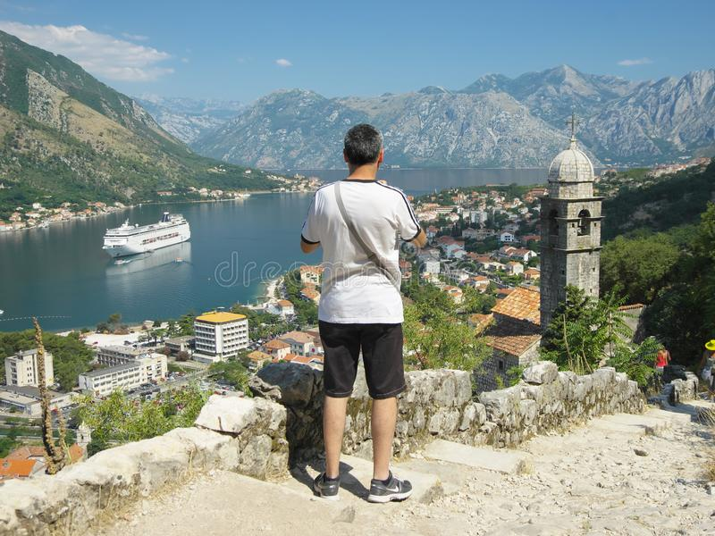 Tourist Looking At Kotor Bay, Montenegro. Kotor, Montenegro - July 18, 2013: a tourist is looking at the landscape of Kotor Bay from above of the church of Our stock photography