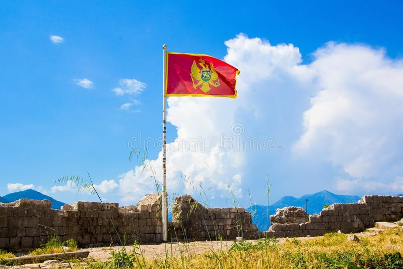 KOTOR MONTENEGRO - JUNI 12, 2015: Vinka i vindflaggan av Montenegro Forntida fästningvägg ovanför Kotor royaltyfria bilder