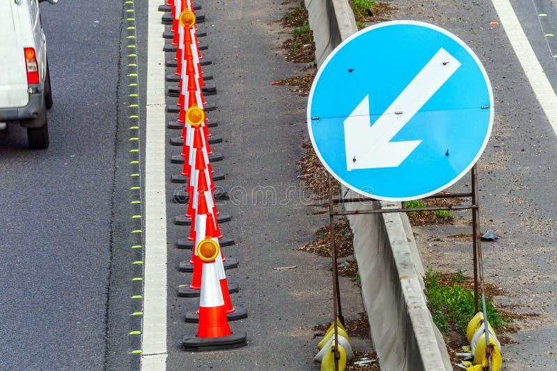 Kottar för Roadworks för UK-vägservice och riktningstecken på motorwayen arkivfoton