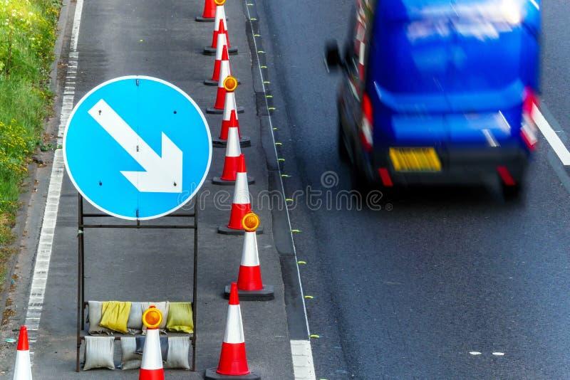 Kottar för Roadworks för UK-vägservice och riktningstecken på motorwayen med blåa skåpbil bortgång arkivfoto