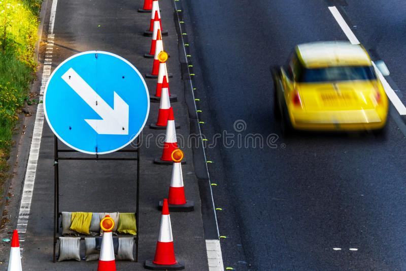 Kottar för Roadworks för UK-vägservice och riktningstecken på motorwayen med gult passera för bil arkivfoto