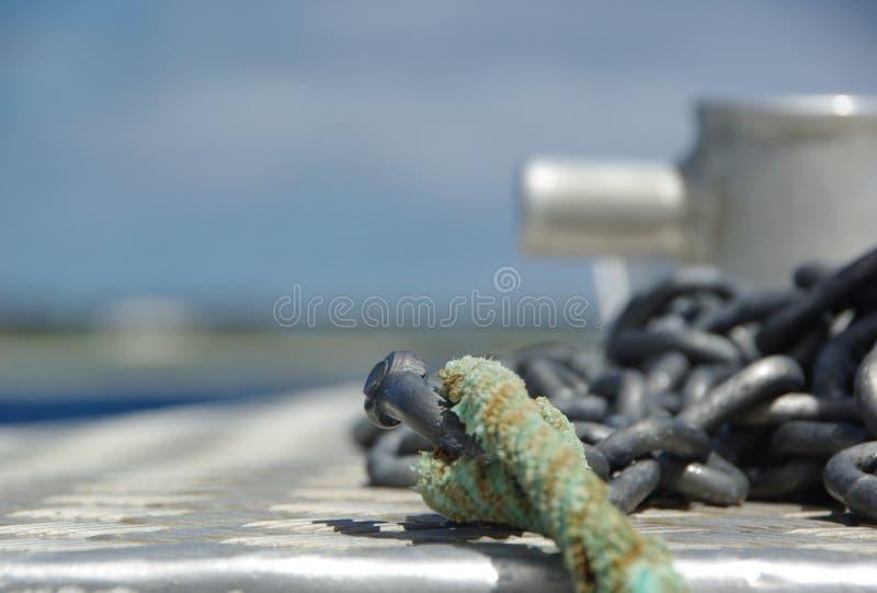 Kotwicowy łańcuch i arkana na przodzie łódź z zakotwiczać punkt w tle fotografia stock