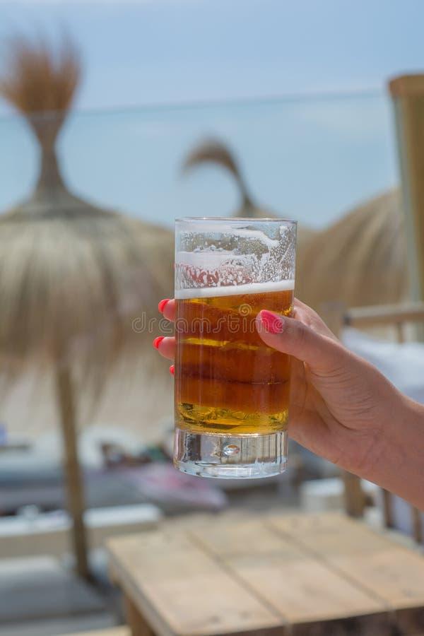 Koud bier in de zomer bij het strand stock foto's