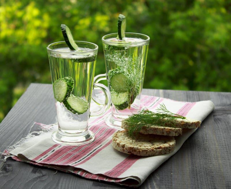Koud drinkwater met komkommer en dille in een glas stock afbeelding