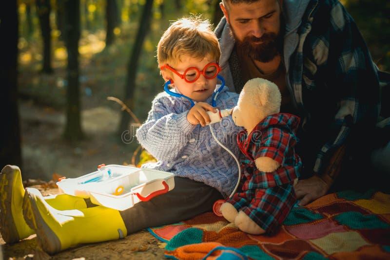 Koud griepseizoen, lopende neus Zowel lachen de papa als het kind De ouder onderwijst baby Het tonen van het zieke kind niezen bi stock afbeeldingen