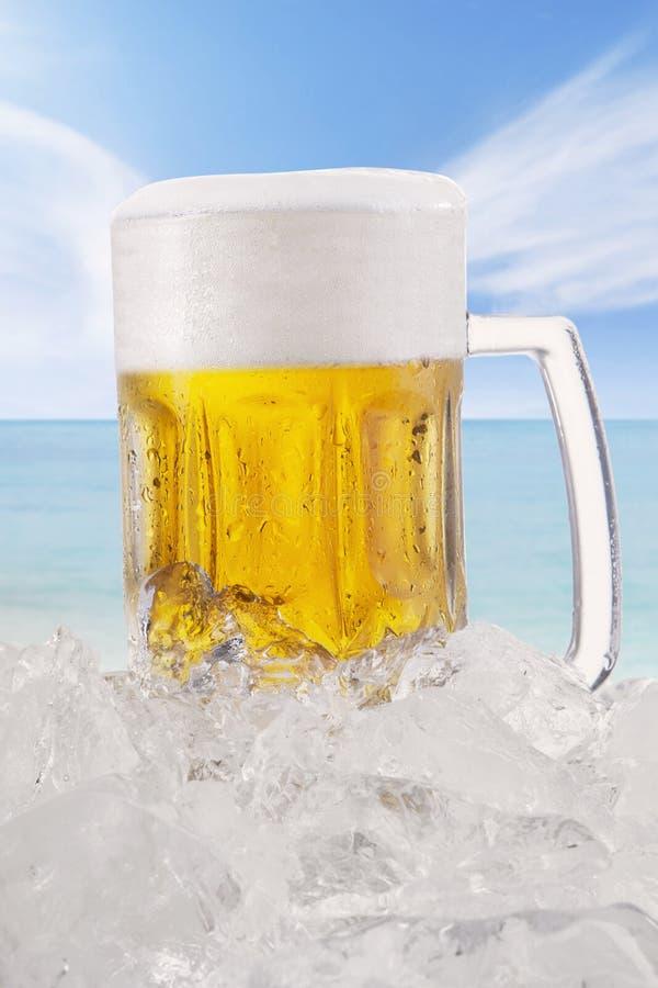Koud lagerbier met schuim in het glas bij strand royalty-vrije stock afbeelding