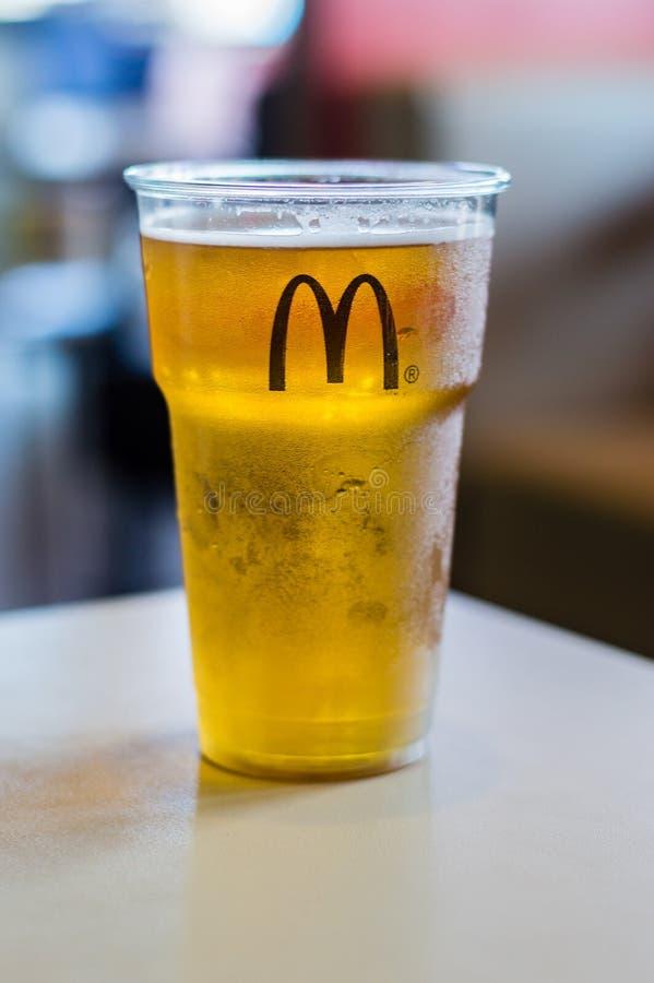 Koud Mahou-bier in een plastic kop met McDonald-embleem Bier in Spaanse McDonald wordt gediend die stock foto's