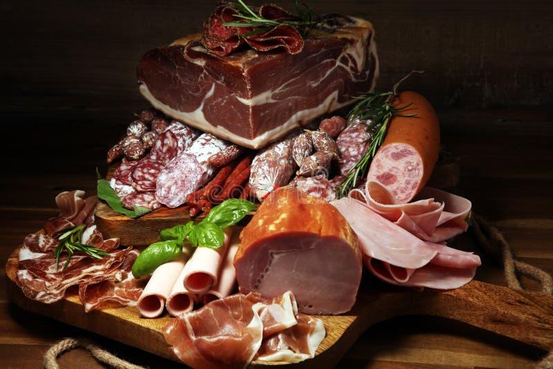 Koud vleesassortiment met heerlijke salami en verse kruiden Verscheidenheid van vleeswaren met inbegrip van coppa en worsten royalty-vrije stock foto's
