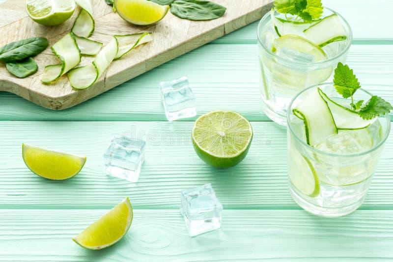 Koud water met ijs, komkommer en citroensap voor de zomer gezonde drank op munt groene houten achtergrond royalty-vrije stock fotografie