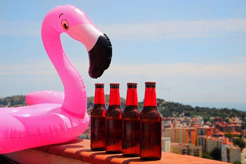 Koude bieren naast een flamingovlotter stock afbeeldingen
