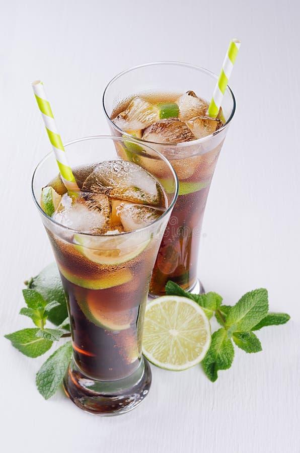 Koude cocktail Cuba libre in twee natte glazen met stro, stukkenkalk, munt op zachte moderne witte achtergrond, hoogste mening, c royalty-vrije stock foto's