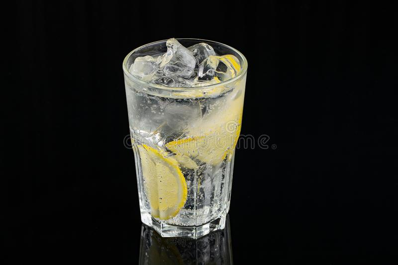 Koude cocktail met citroen Een glas van dauwdalingen Versheid, alcohol, bar Zwarte achtergrond stock afbeeldingen