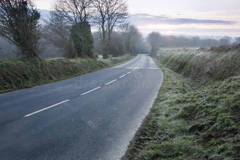 Koude dageraad op een kleine weg in Frankrijk op een koude mistige dag, vroeg in de ochtend stock foto's