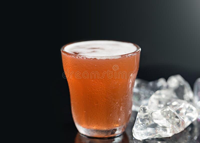 Koude drank met bevroren kubus op zwarte achtergrond royalty-vrije stock afbeelding