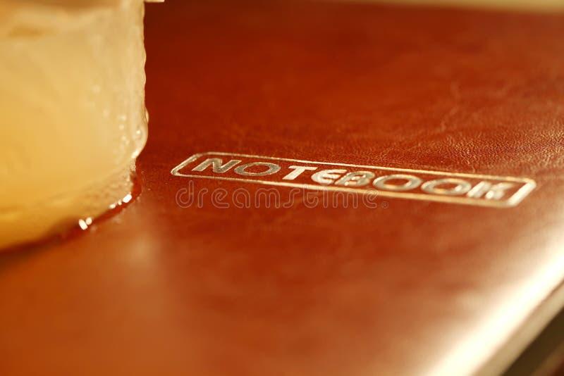 Koude drank plastic kop gezet op notitieboekjescène royalty-vrije stock foto's