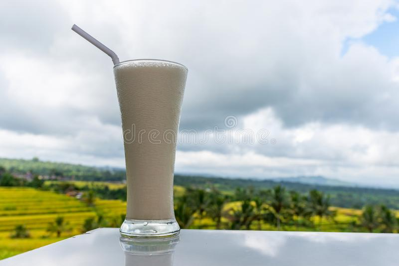 Koude en verse milkshake op de het gebiedsachtergrond van rijstterrassen stock afbeeldingen