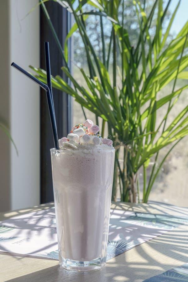 Koude milkshake met aardbeien en heemst, op een houten lijst tegen een palm en zandig stock afbeeldingen