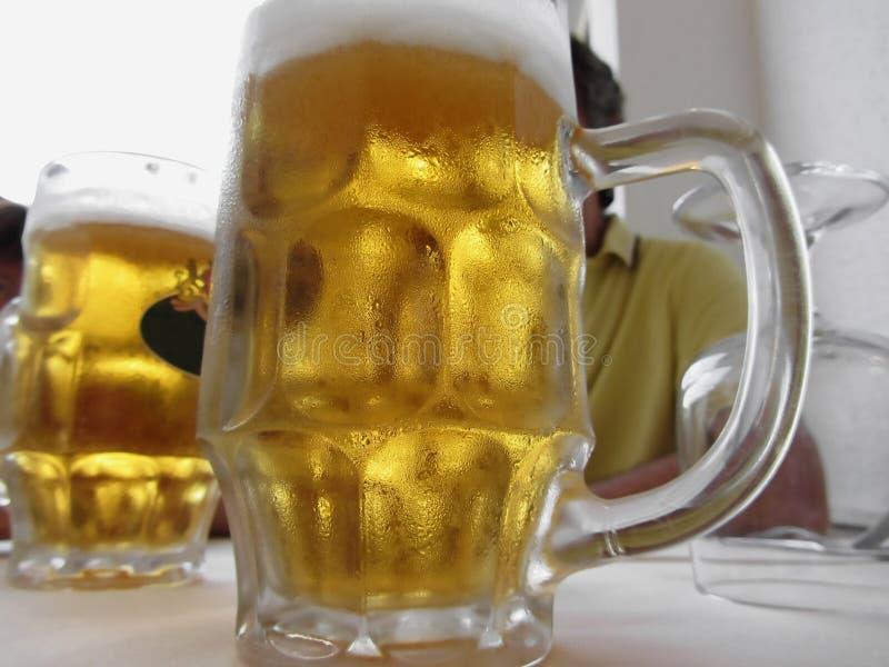 Koude mok licht bier op de lijst bij een restaurant stock afbeelding