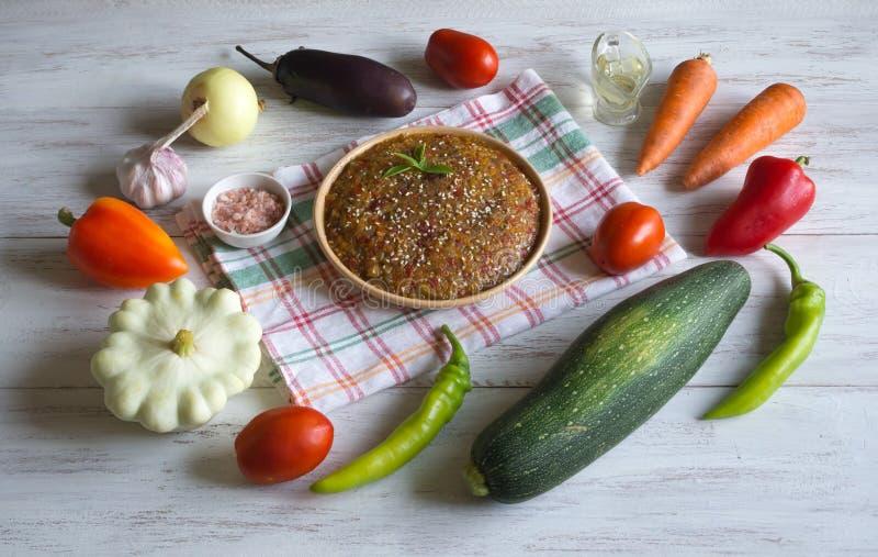 Koude plantaardige snack in een plaat en groenten op een witte houten lijst stock foto